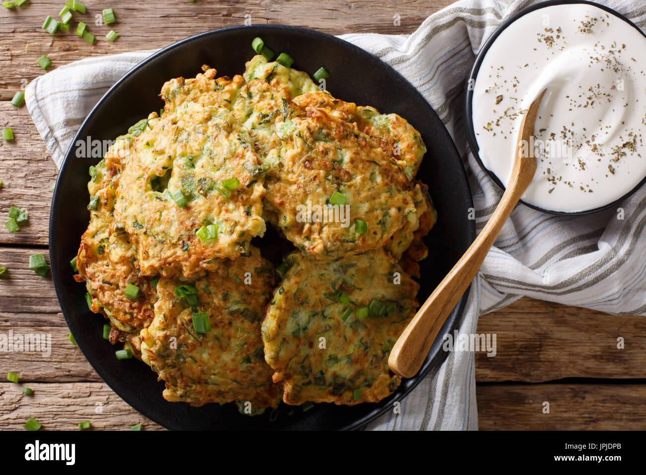 Appena cotte le zucchine frittelle con panna acida vicino sul tavolo. Vista orizzontale dal di sopra Immagini Stock