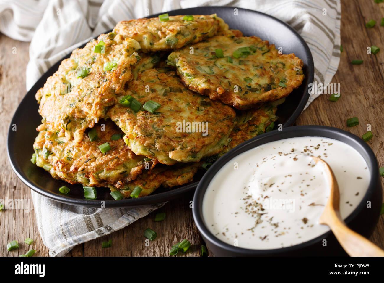 Zucchine deliziose frittelle con panna acida vicino sul tavolo orizzontale. Immagini Stock