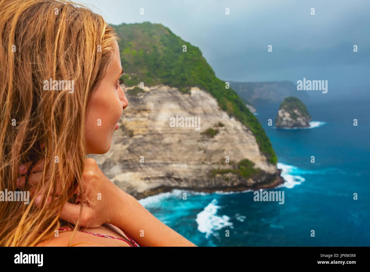 Vacanza per la famiglia lifestyle.Donna stand ad alta rupe sotto il cielo piovoso. Guarda alla spiaggia con mare surf sotto le rocce. Destinazione di viaggio in Nusa Penida, Bali Immagini Stock