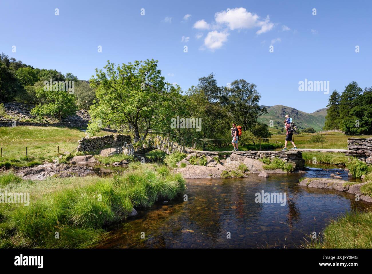 Due Padri il trasporto di bambini nel baby carrier su Slater's Bridge & River Brathay in poco Langdale nel Lake District inglese, Cumbria Immagini Stock