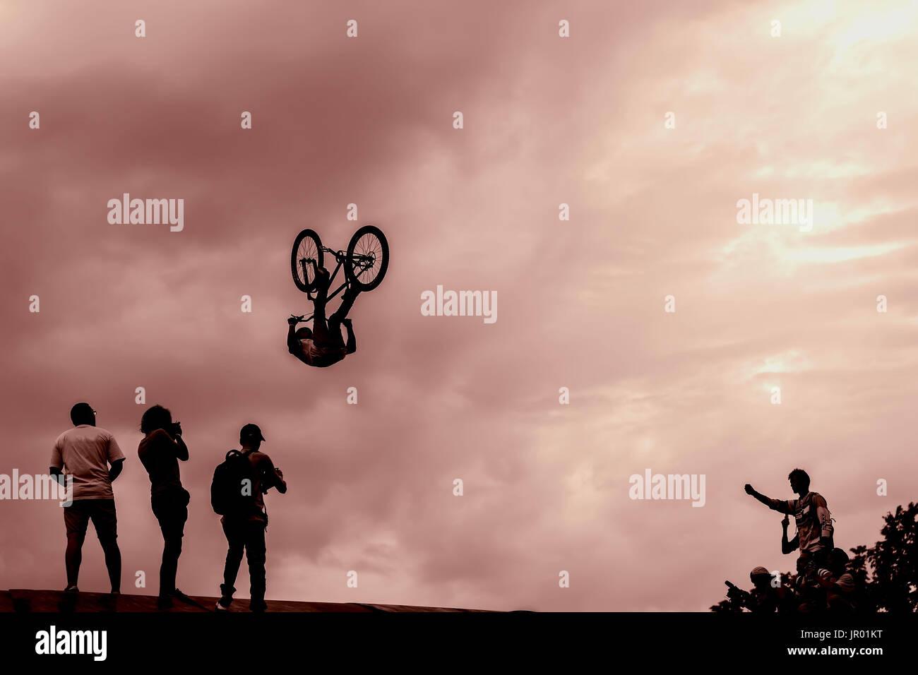 Extrem Sport e rischio. Prestazioni a concorsi. Silhouette di giovani non identificato uomo compie acrobazie sullo sfondo del cielo vividi. Con posto per il tuo testo per lo sfondo Immagini Stock