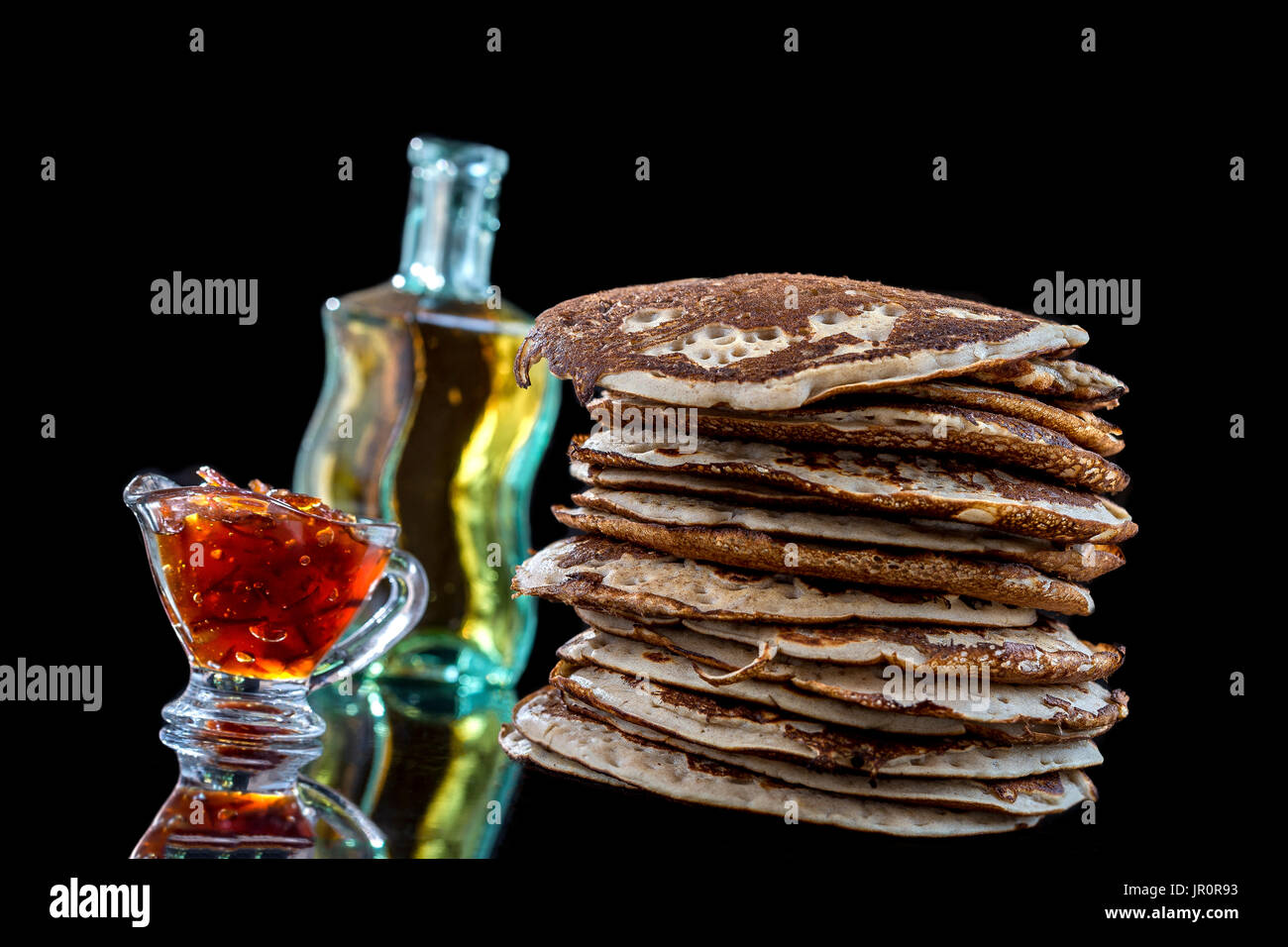 Glutten-free frittelle con marmellata e sciroppo d'acero, bio ingredienti salutari, su nero Immagini Stock