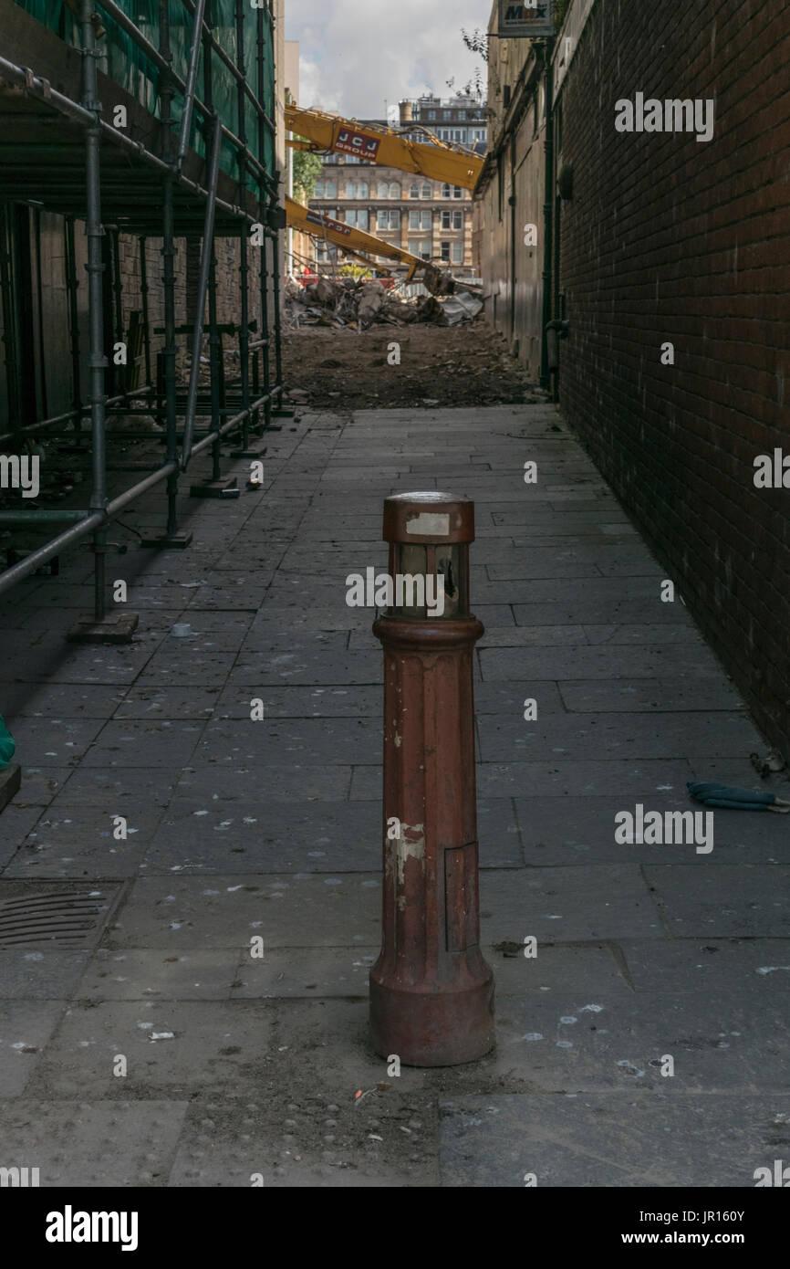 Il vecchio pavimento in metallo post nel vicolo che conduce a lavori di demolizione, Glasgow, Scotland, Regno Unito Foto Stock