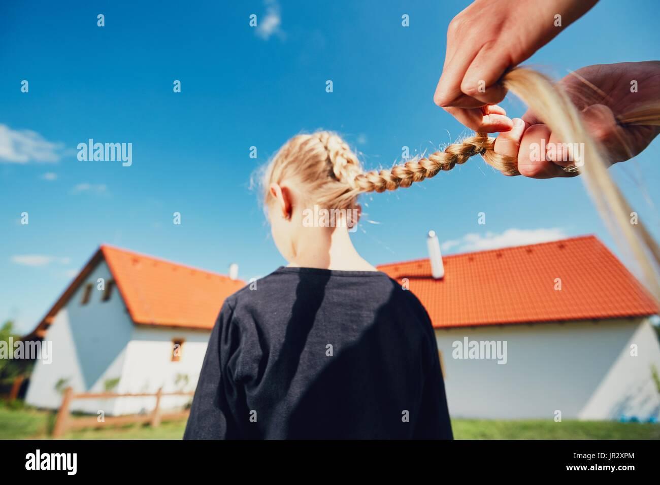 Giovane donna rendendo trecce di capelli della bambina sul giardino in campagna. Immagini Stock