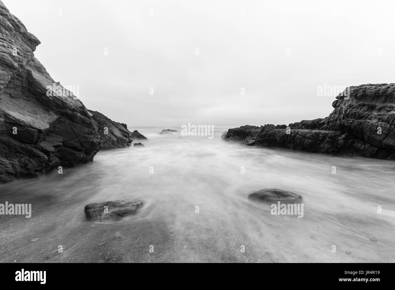 Rocky Malibu Beach con motion blur acqua in bianco e nero. Immagini Stock