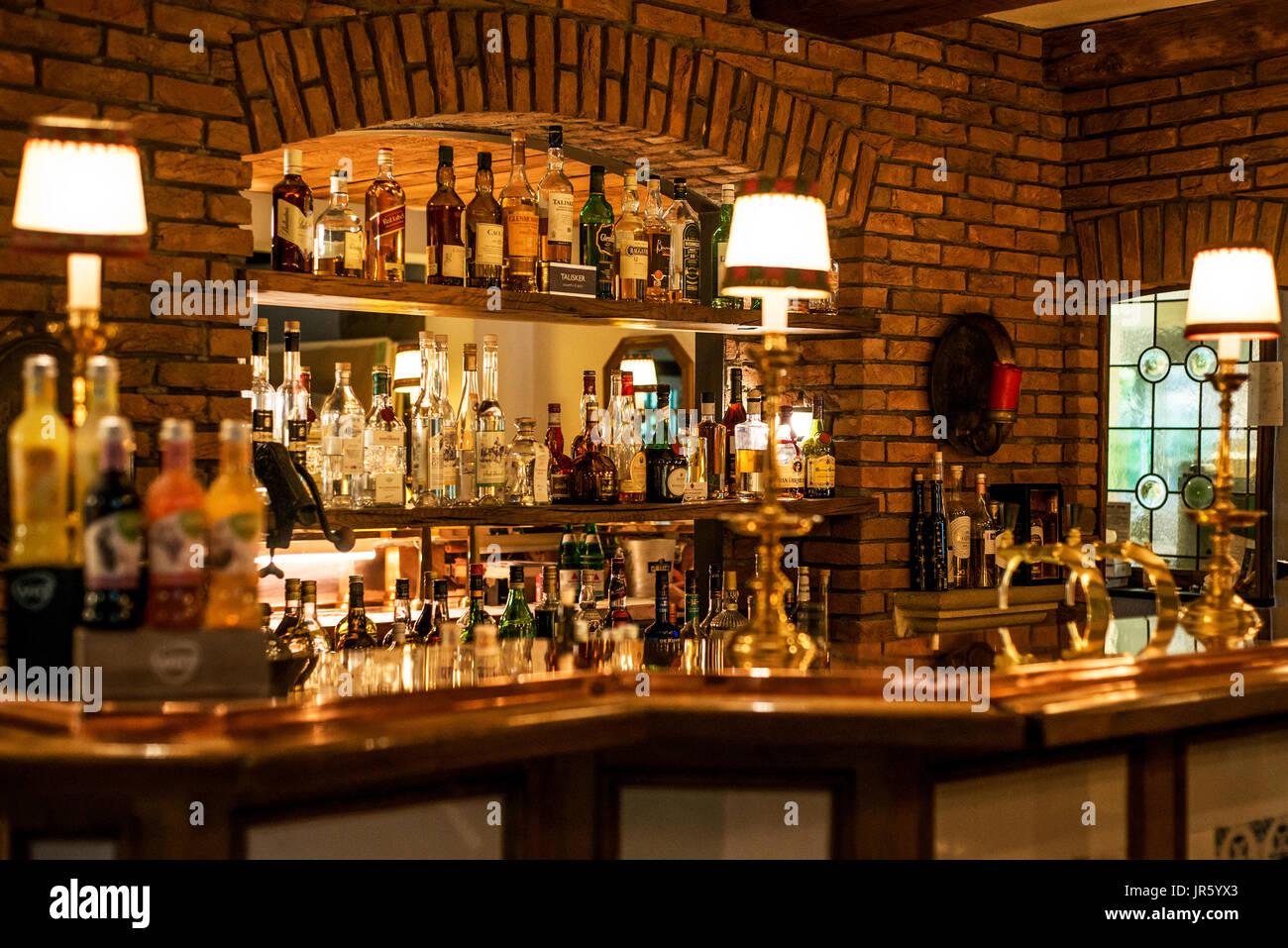 Amari e infusi sul bancone, bottiglie di sfocare lo sfondo immagine nei toni del muro di mattoni in ambiente di luce Immagini Stock