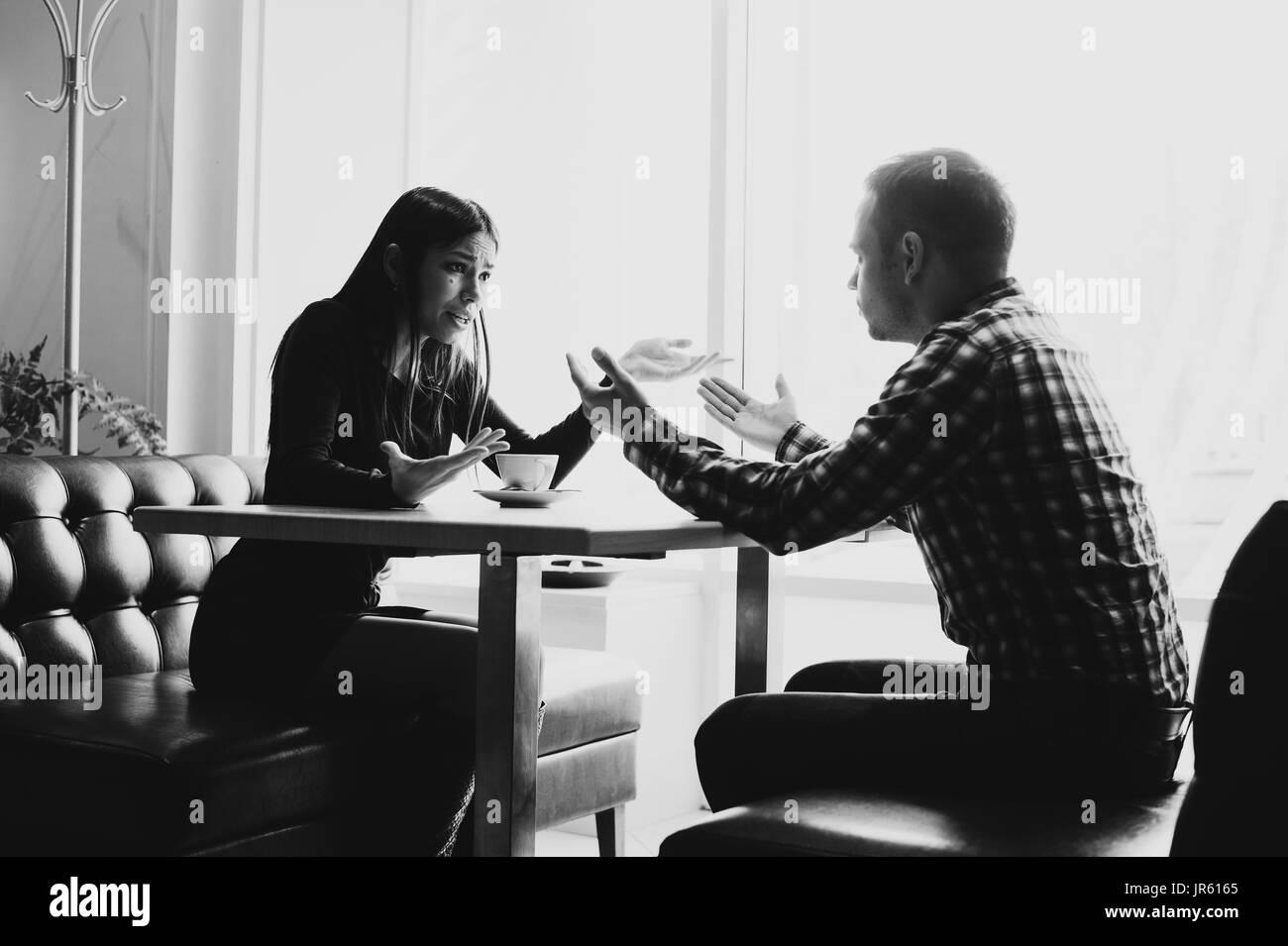 L uomo e la donna nelle discussioni del ristorante Immagini Stock