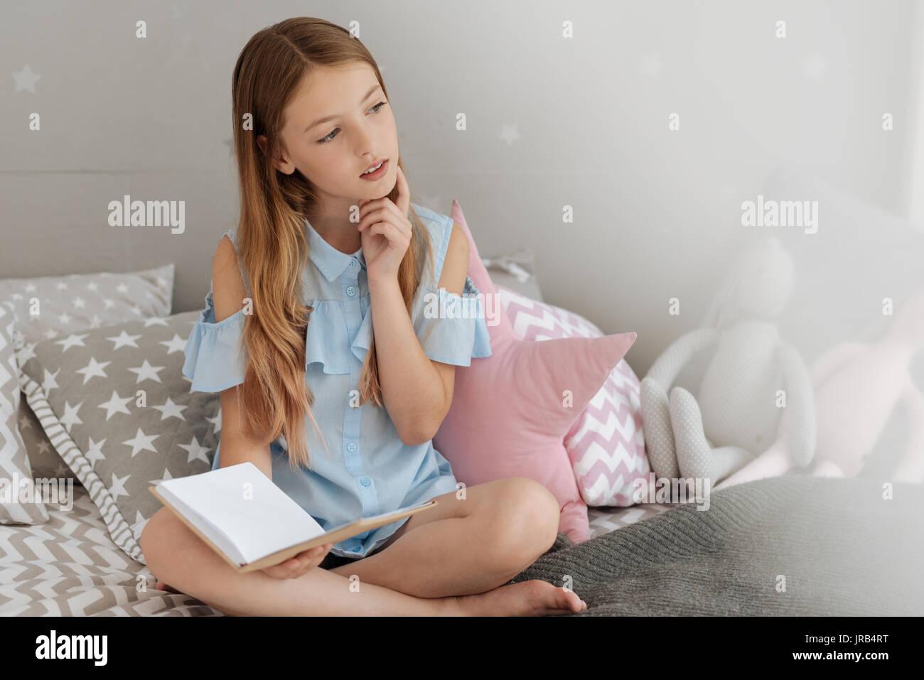 Curioso schoolgirl pensando a qualcosa di Immagini Stock
