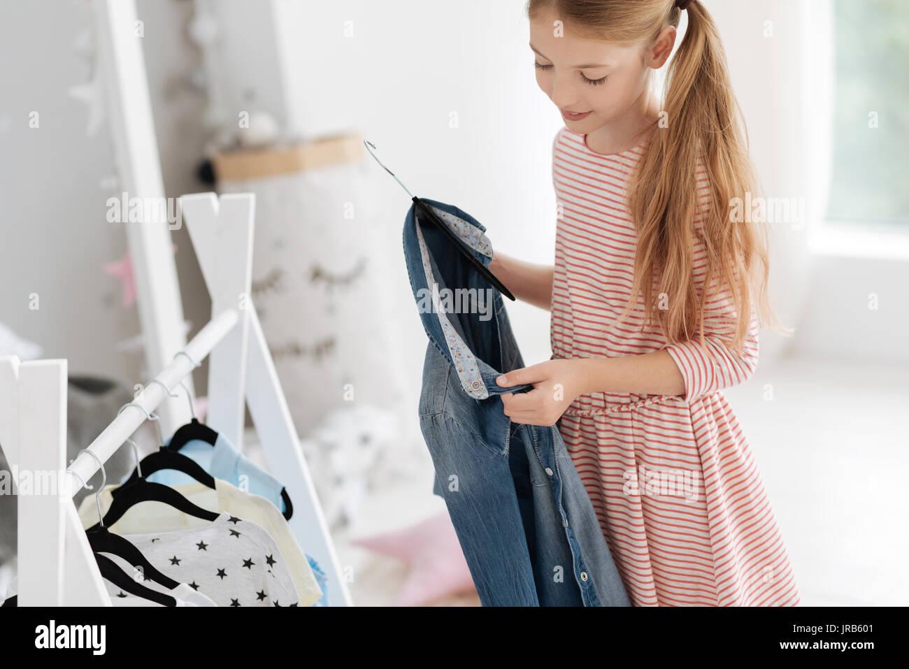 Signora giovane guardando il denim shirt mentre scegliendo outfit Immagini Stock
