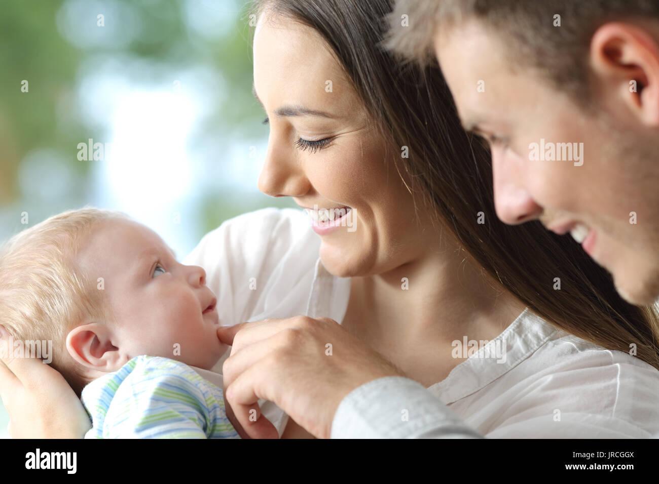 Orgogliosi genitori tenendo il loro bambino un cercando di lui Immagini Stock