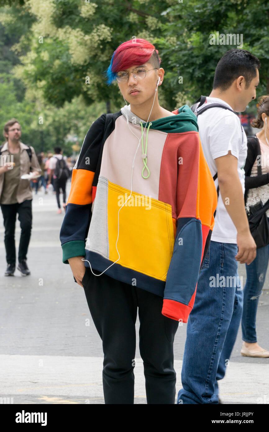 Un giovane uomo con capelli colorati e un colorato felpa in piedi su un angolo nel centro cittadino di Manhattan, a New York City, Immagini Stock