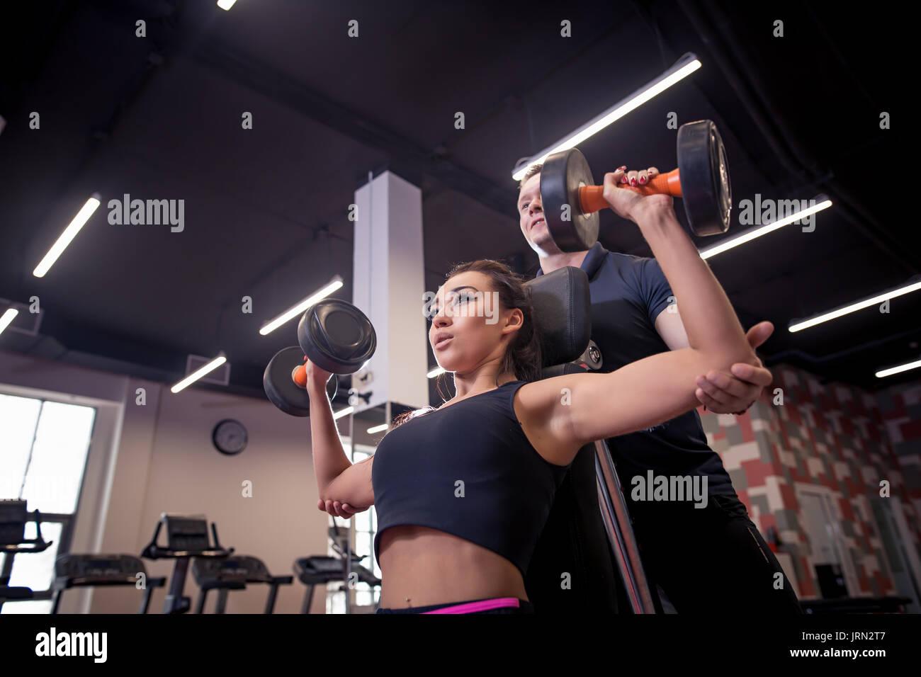 Palestra donna personal trainer uomo con peso di apparecchiature per il training Foto Stock