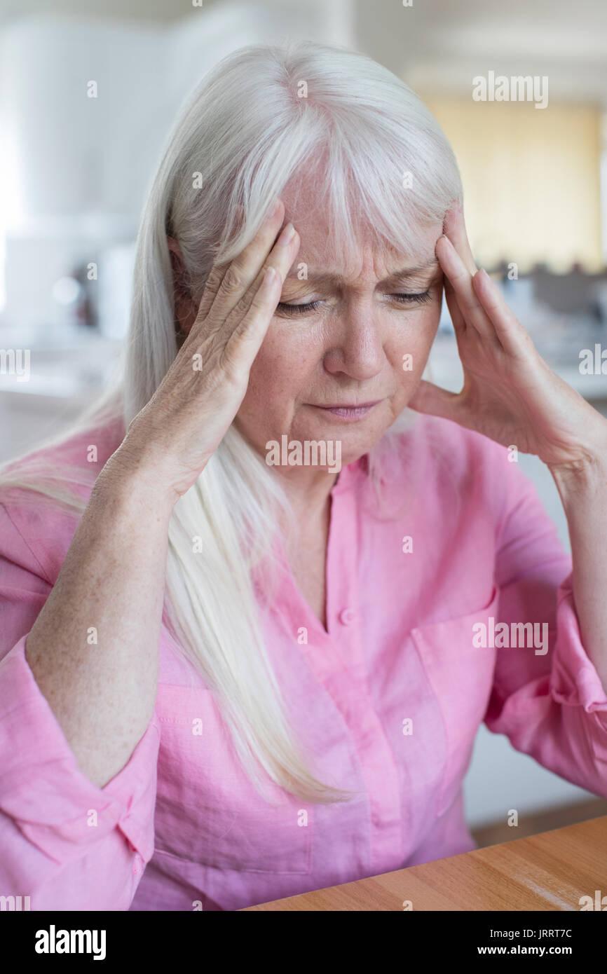 Donna matura a casa che soffrono di mal di testa Immagini Stock