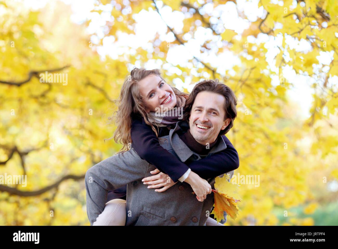 Amore, relazioni stagione e concetto di persone - felice coppia giovane divertendosi in autunno park piggyback ride Immagini Stock