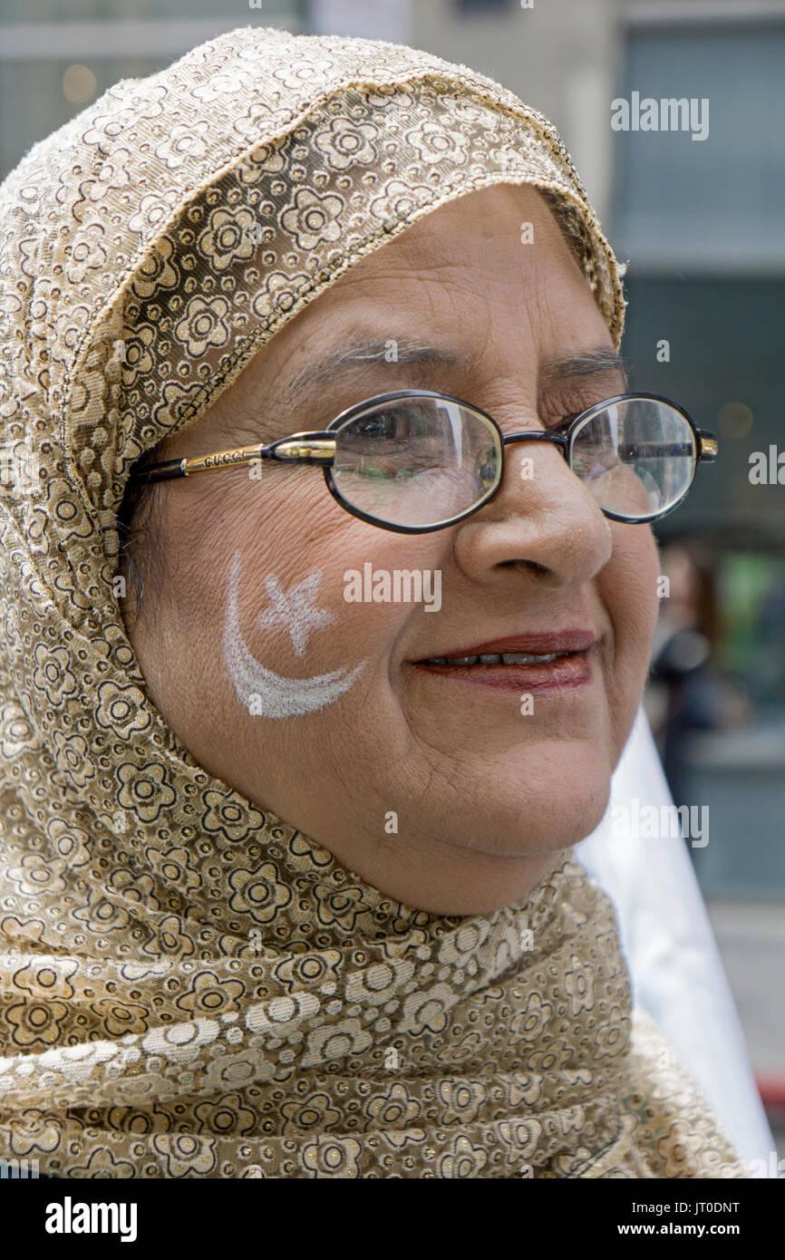 Una donna con la bandiera pakistana simboli dipinti sulla sua guancia al Pakistan annuale parata del giorno Midown ioni di Manhattan, New York City. Immagini Stock