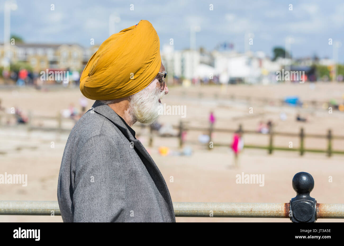 La religione sikh testa di uomo con turbante in piedi presso la costa guardando la spiaggia a sud dell'Inghilterra, Regno Unito. Immagini Stock