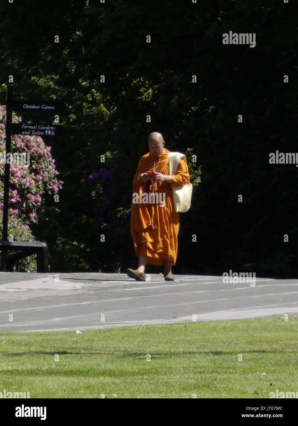 Un monaco buddista per ascoltare musica su un iphone Foto Stock