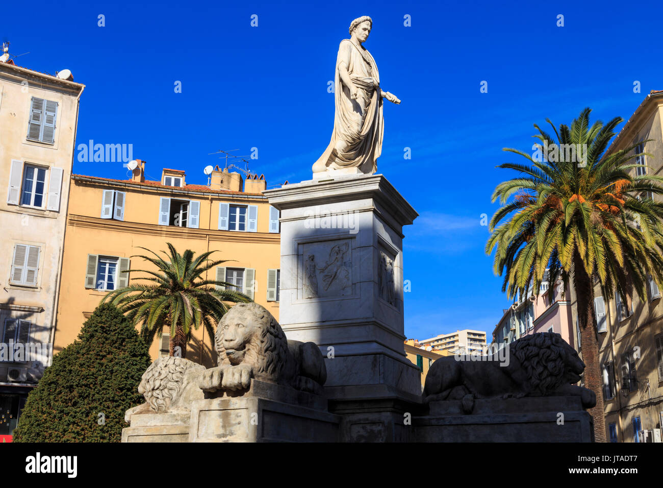 Statua di Napoleone come imperatore romano, con i lions e palme, edifici color pastello, Place Foch, Ajaccio, Isola Foto Stock