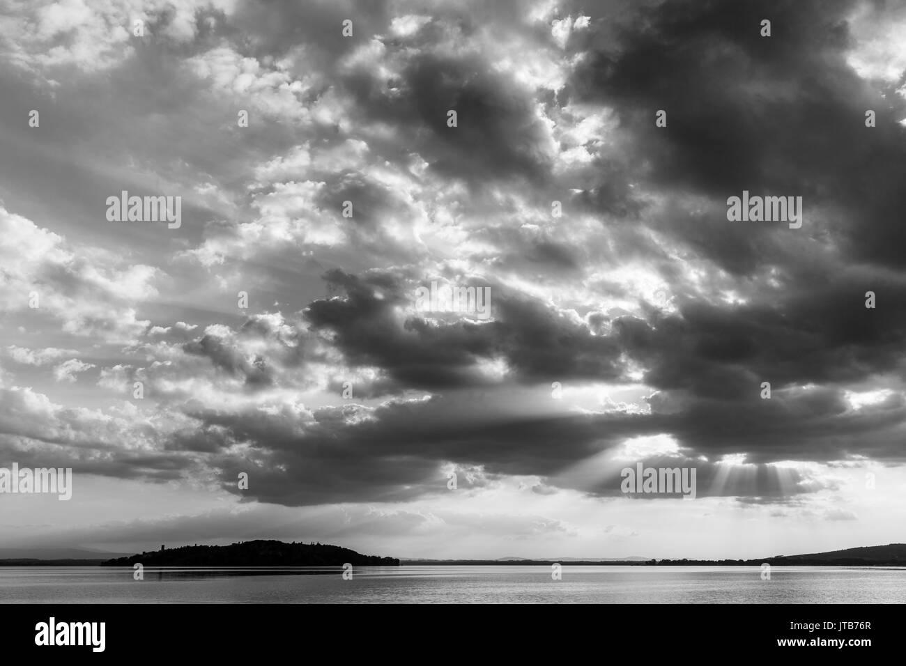 Raggi di sole che fuoriesce attraverso le nuvole sopra un isola in un lago Immagini Stock