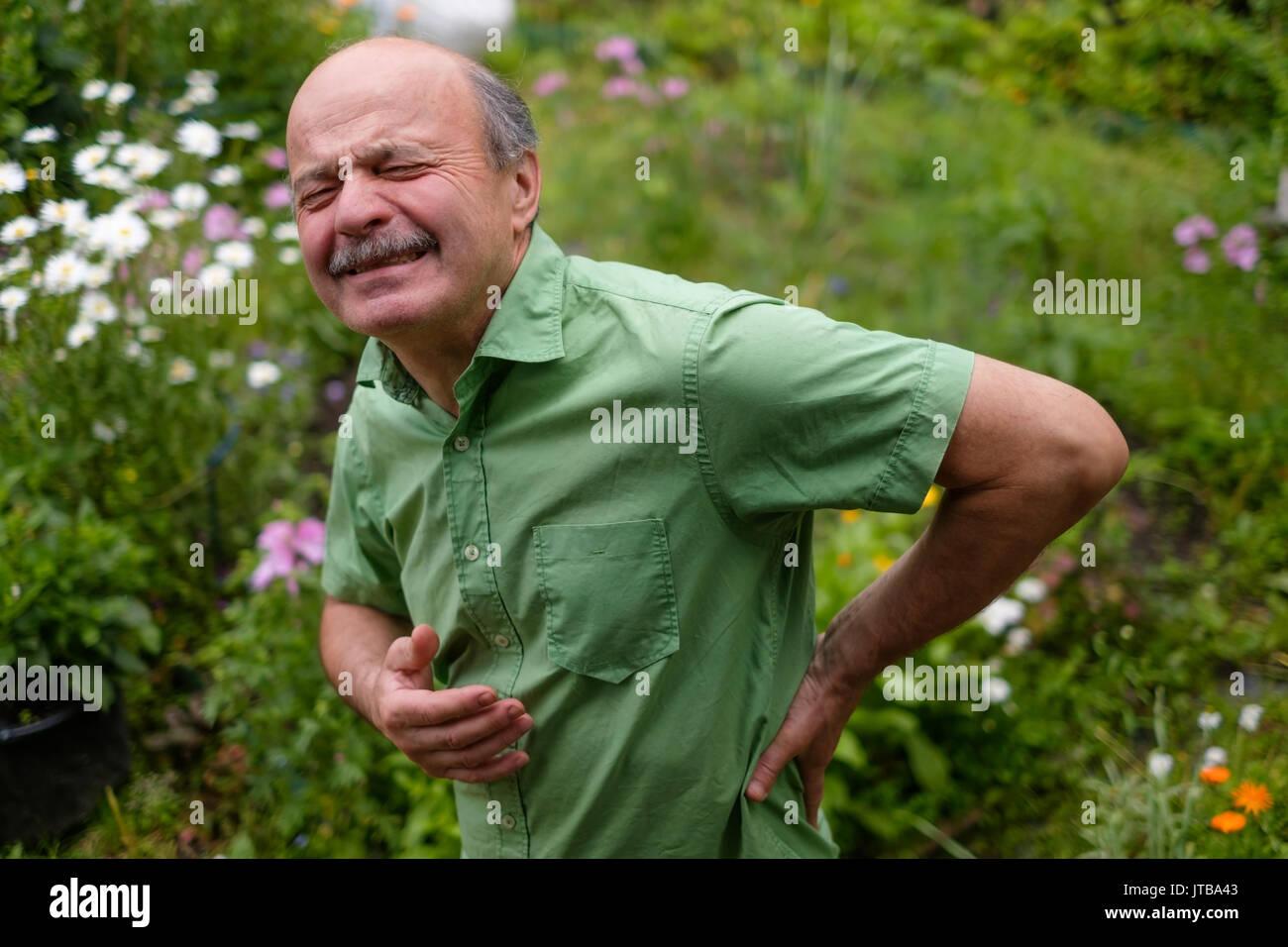 Il vecchio uomo avente lombaggine dolore Immagini Stock