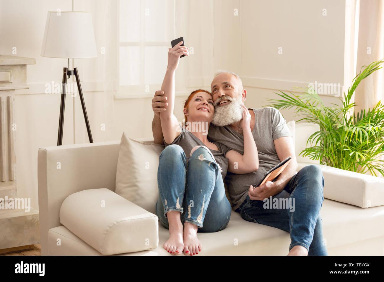 Felice Coppia matura tenendo selfie comodamente seduti sul divano di casa Immagini Stock