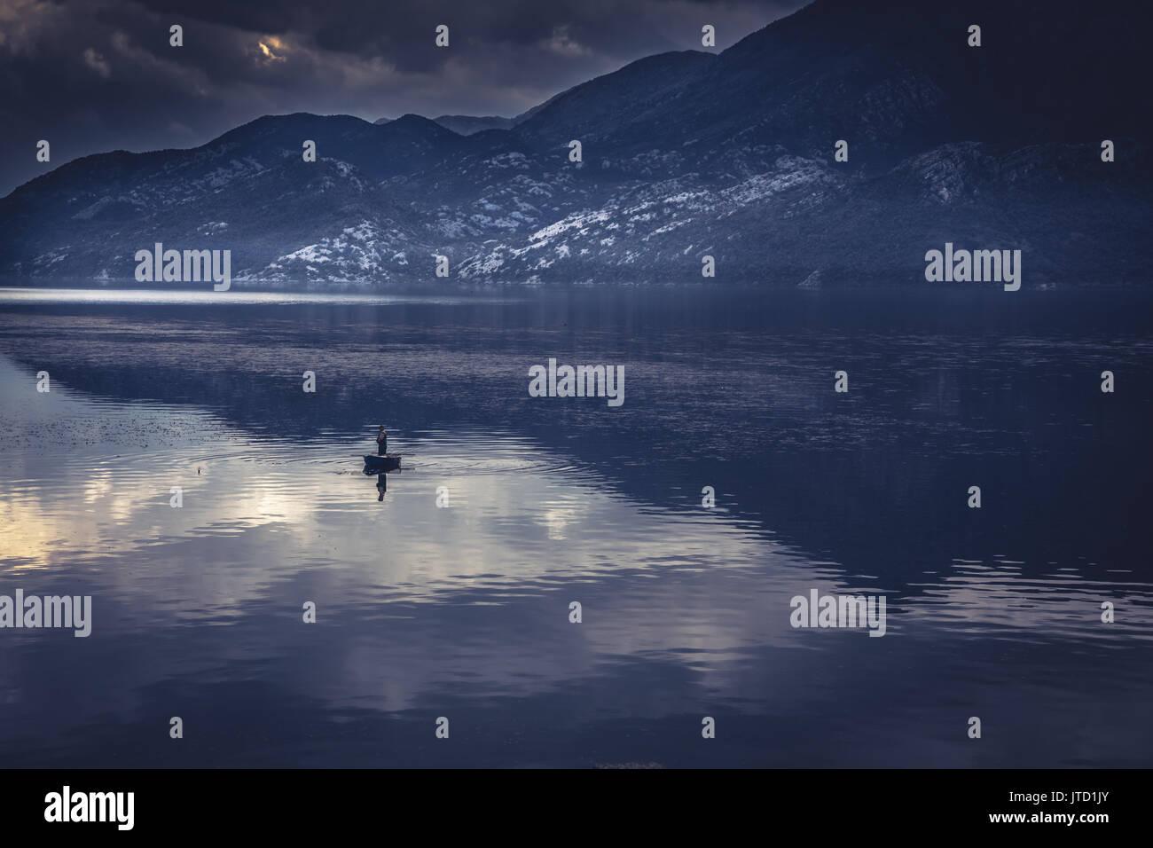 Idilliaco paesaggio di montagna con uomo in barca da pesca nel mezzo di un tranquillo lago con acqua riflessioni durante il sunrise con drammatico nel cielo blu a Immagini Stock