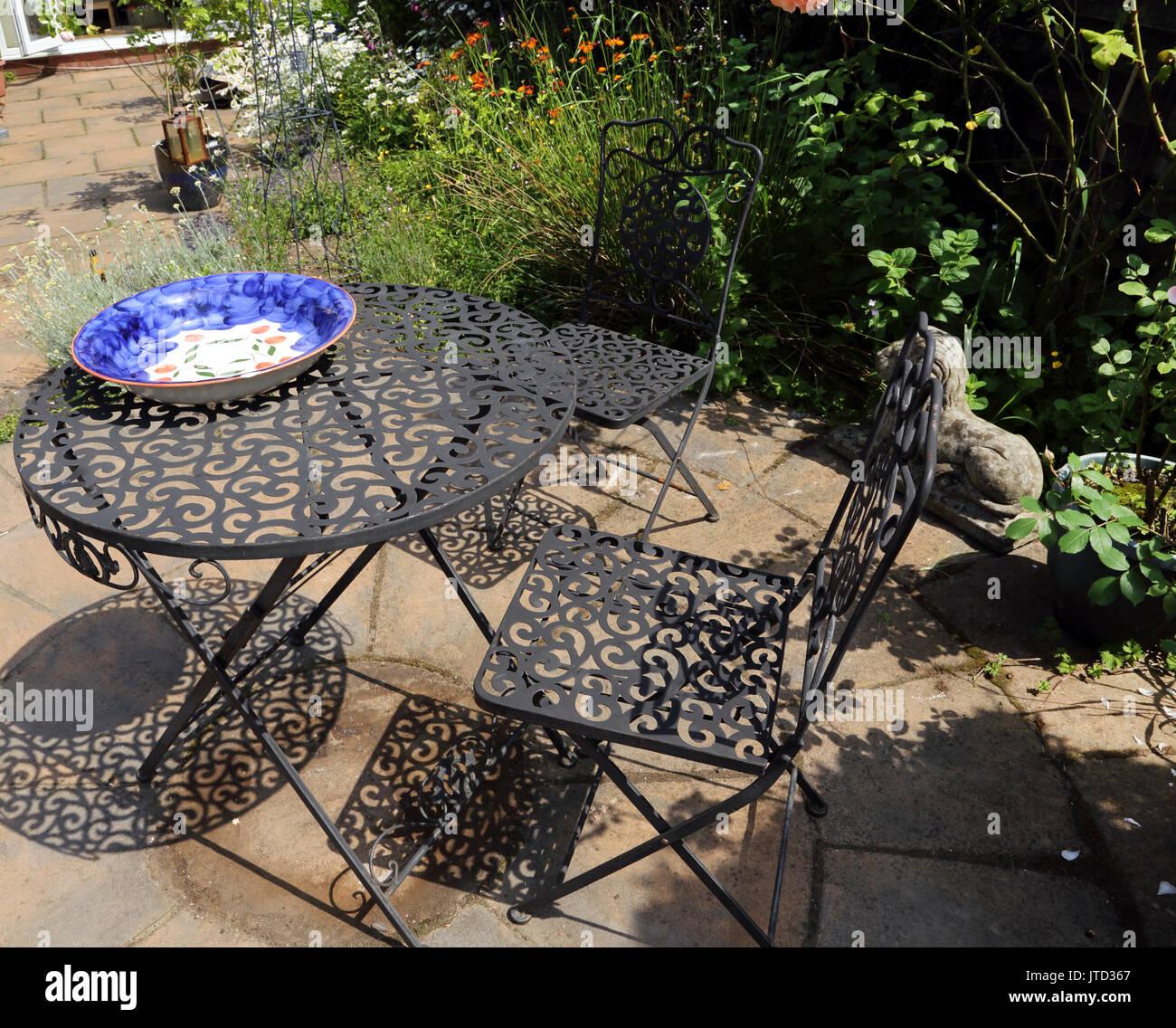 Ferro battuto mobili da giardino e le ombre in estate Birmingham West Midlands England Immagini Stock