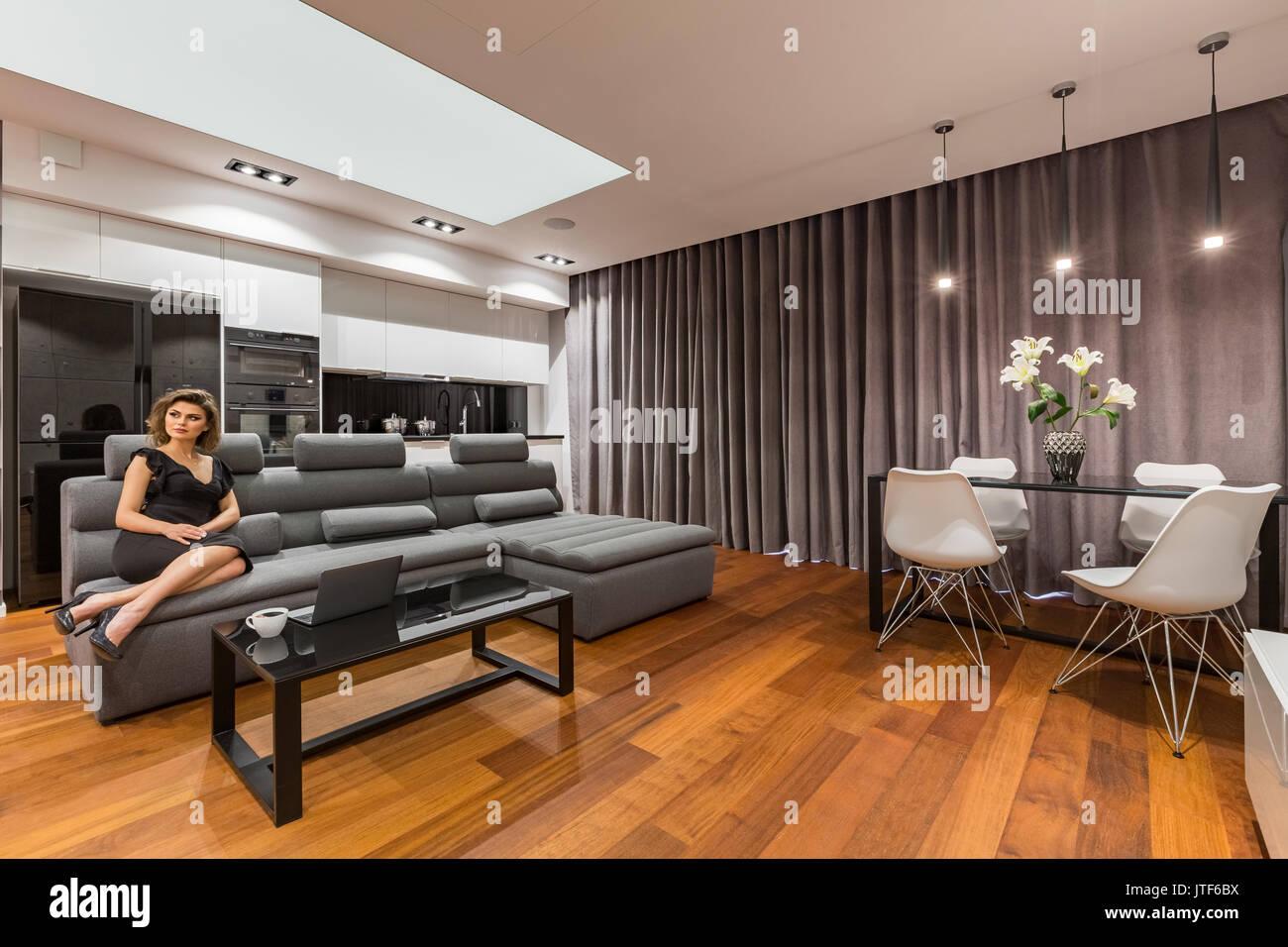 Eleganti Donna seduta sul divano nel soggiorno moderno con cucina ...