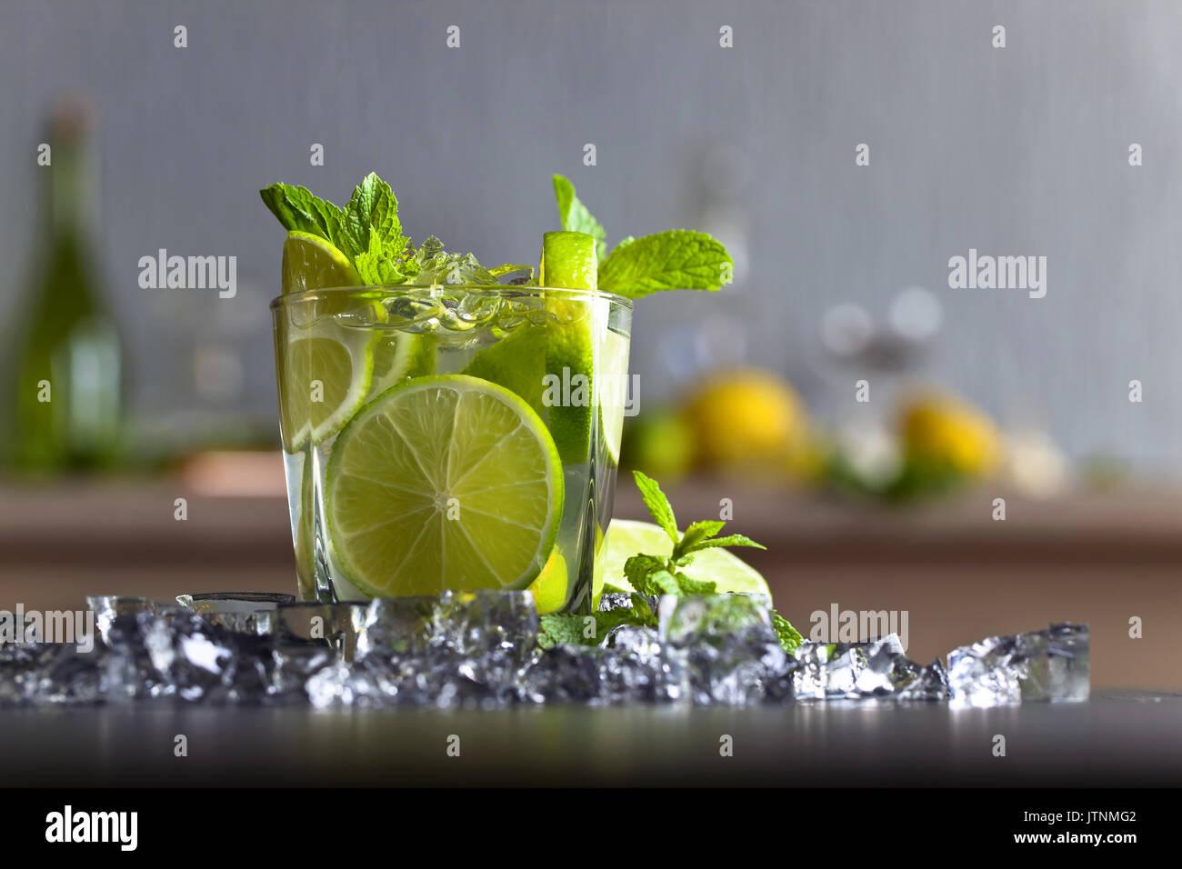 Cocktail con calce , ghiaccio e foglie di menta piperita su una tavola nera . Immagini Stock