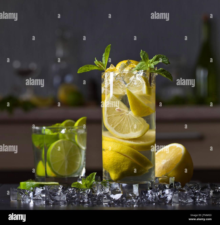 Cocktail con calce , Limone , ghiaccio e foglie di menta piperita su una tavola nera .Copia spazio. Immagini Stock