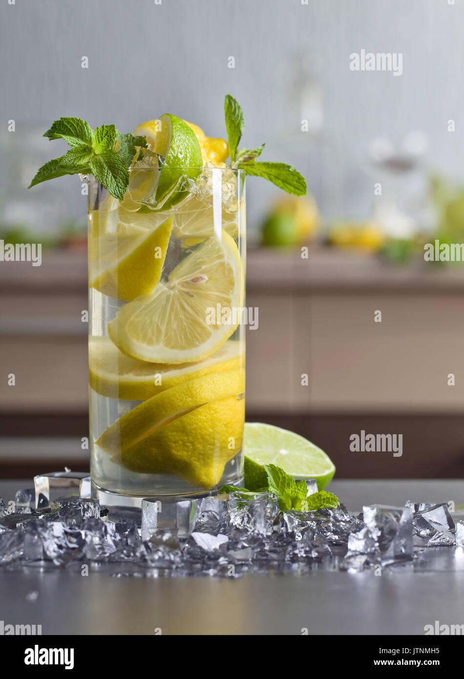 Cocktail con calce , Limone , ghiaccio e foglie di menta piperita su una tavola nera . Immagini Stock