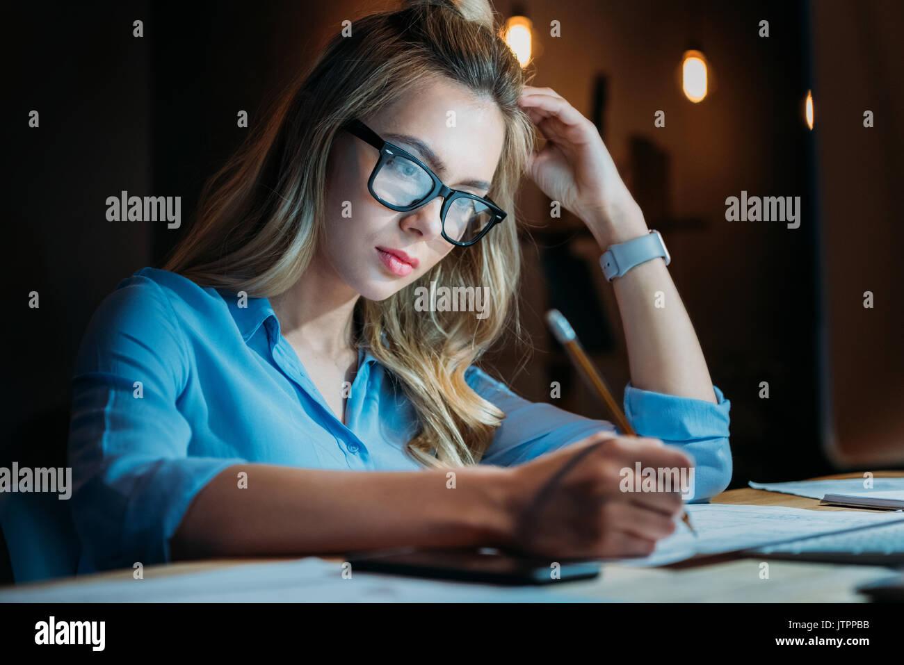 Stanco bionda studente caucasici in occhiali a scrivere qualcosa con la matita e studiare fino a tardi Immagini Stock