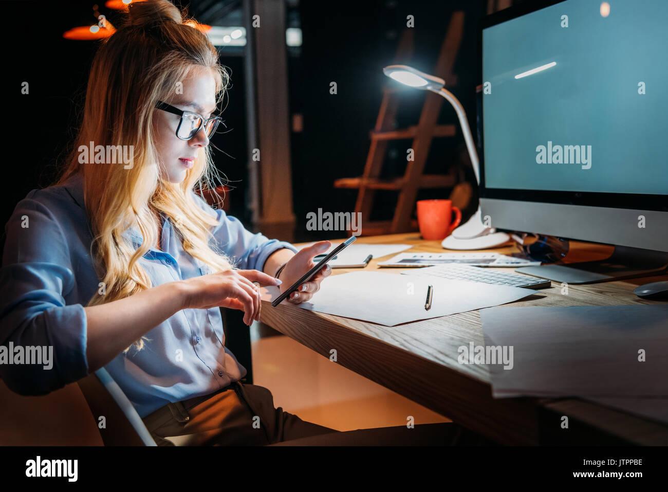 Bionda e giovane imprenditrice caucasici in occhiali utilizza lo smartphone e seduti al posto di lavoro con il computer Immagini Stock