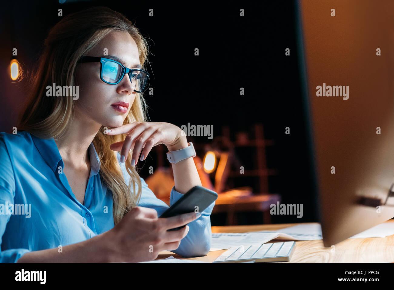 Ritratto di imprenditrice utilizza lo smartphone mentre si lavora fino a tardi in ufficio Immagini Stock