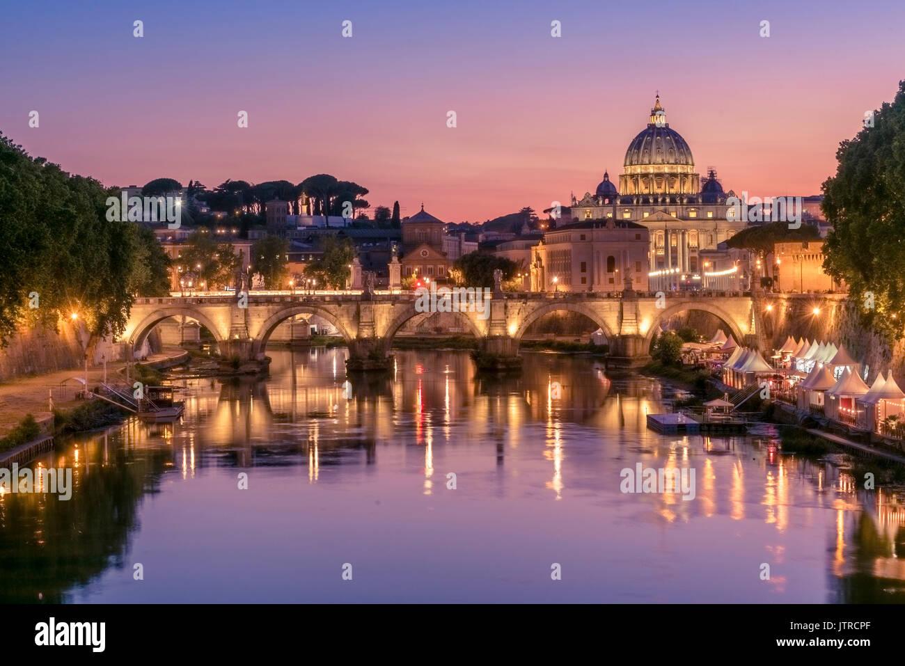 Vista di un tramonto mozzafiato impostazione dietro la Città del Vaticano da Ponte Umberto I, Roma, Italia Foto Stock