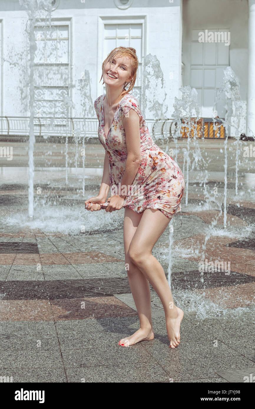 Donna bagnata si asciuga il suo abito, gioca in una fontana e si ...