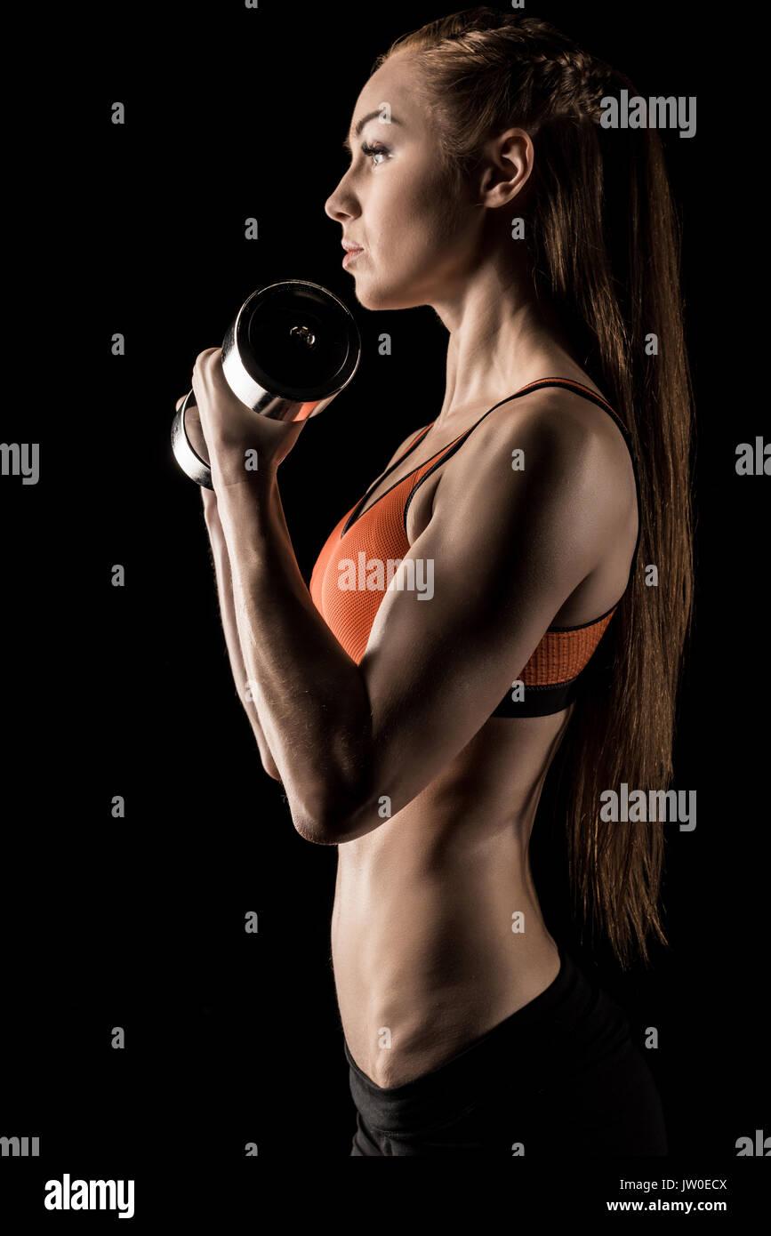 Vista laterale della muscolatura giovane donna che esercitano con il manubrio isolato su nero Immagini Stock