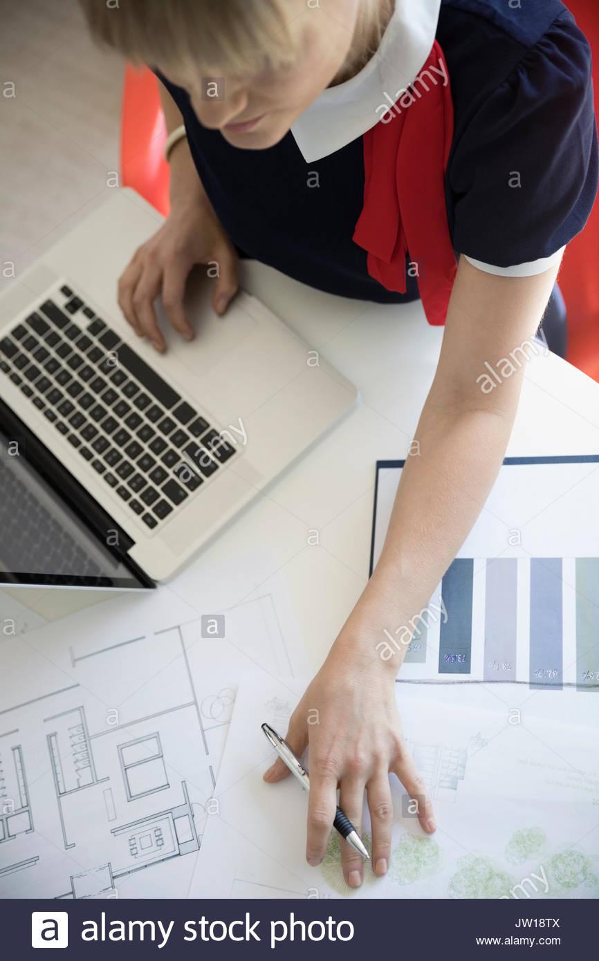 Vista aerea architetto femmina rivedendo blueprint al laptop Immagini Stock