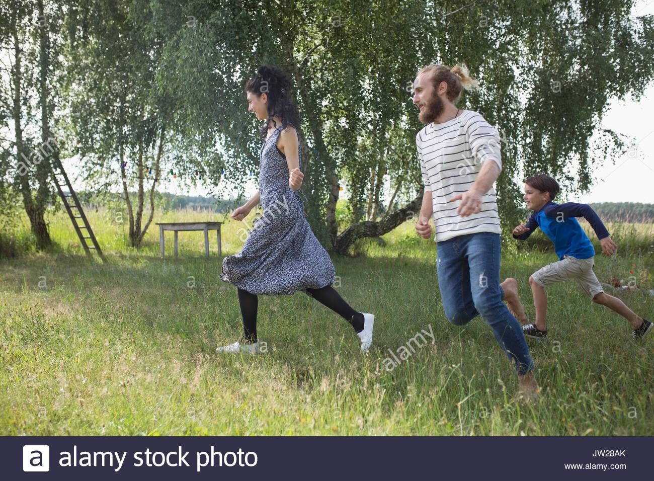 Famiglia giocoso in esecuzione nel cortile rurale Immagini Stock