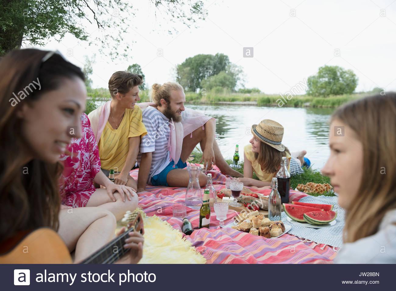 Gli amici e la famiglia rilassante, godendo di picnic estivo a Lakeside Immagini Stock