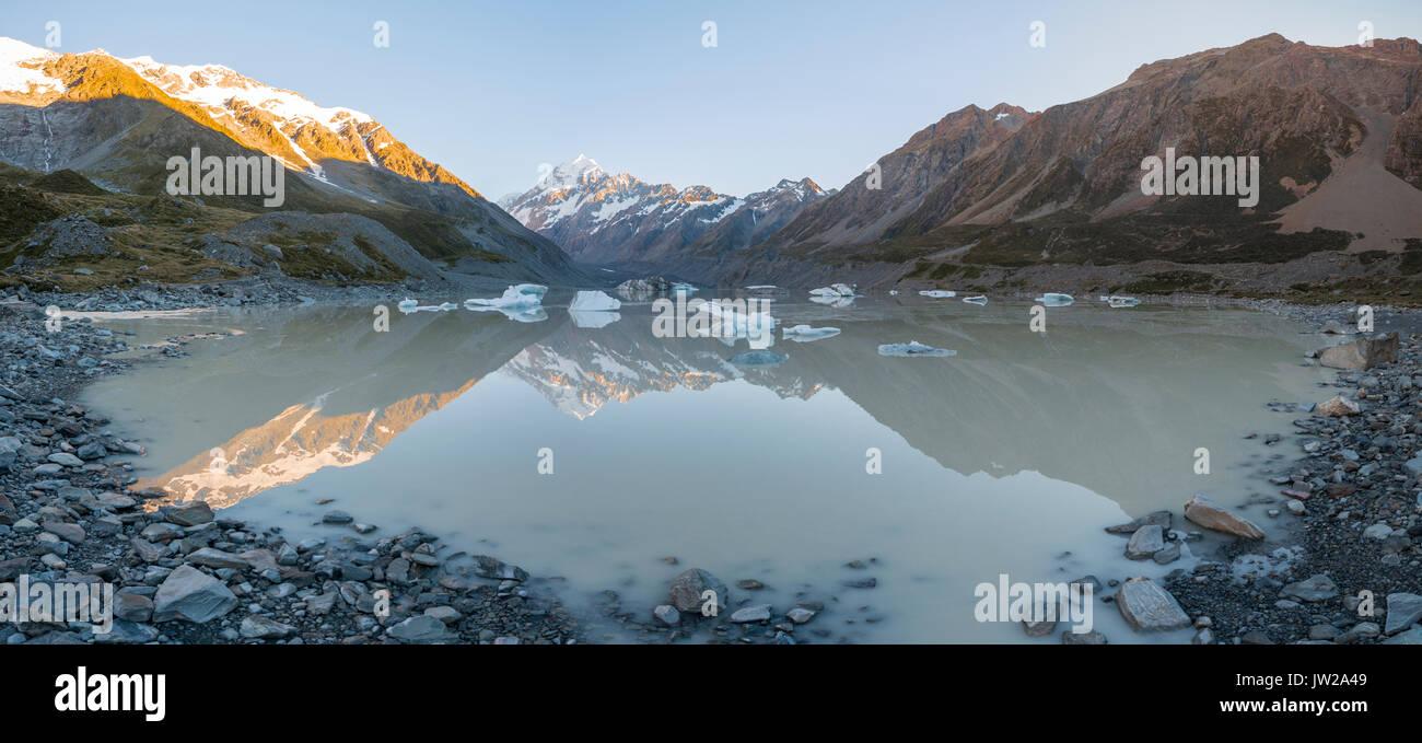 Sunrise, riflessione in Hooker lago, sole di mattina illuminando il Mount Cook, parco nazionale di Mount Cook, Alpi del Sud, Hooker Valley Immagini Stock