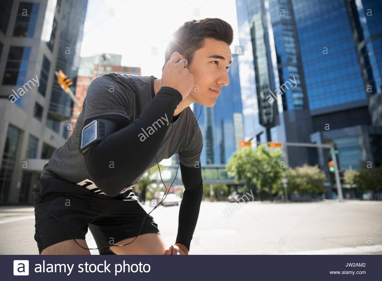 Giovane maschio runner in appoggio, l'ascolto di musica con cuffie e lettore mp3 fascia braccio sulla soleggiata strada urbana Immagini Stock