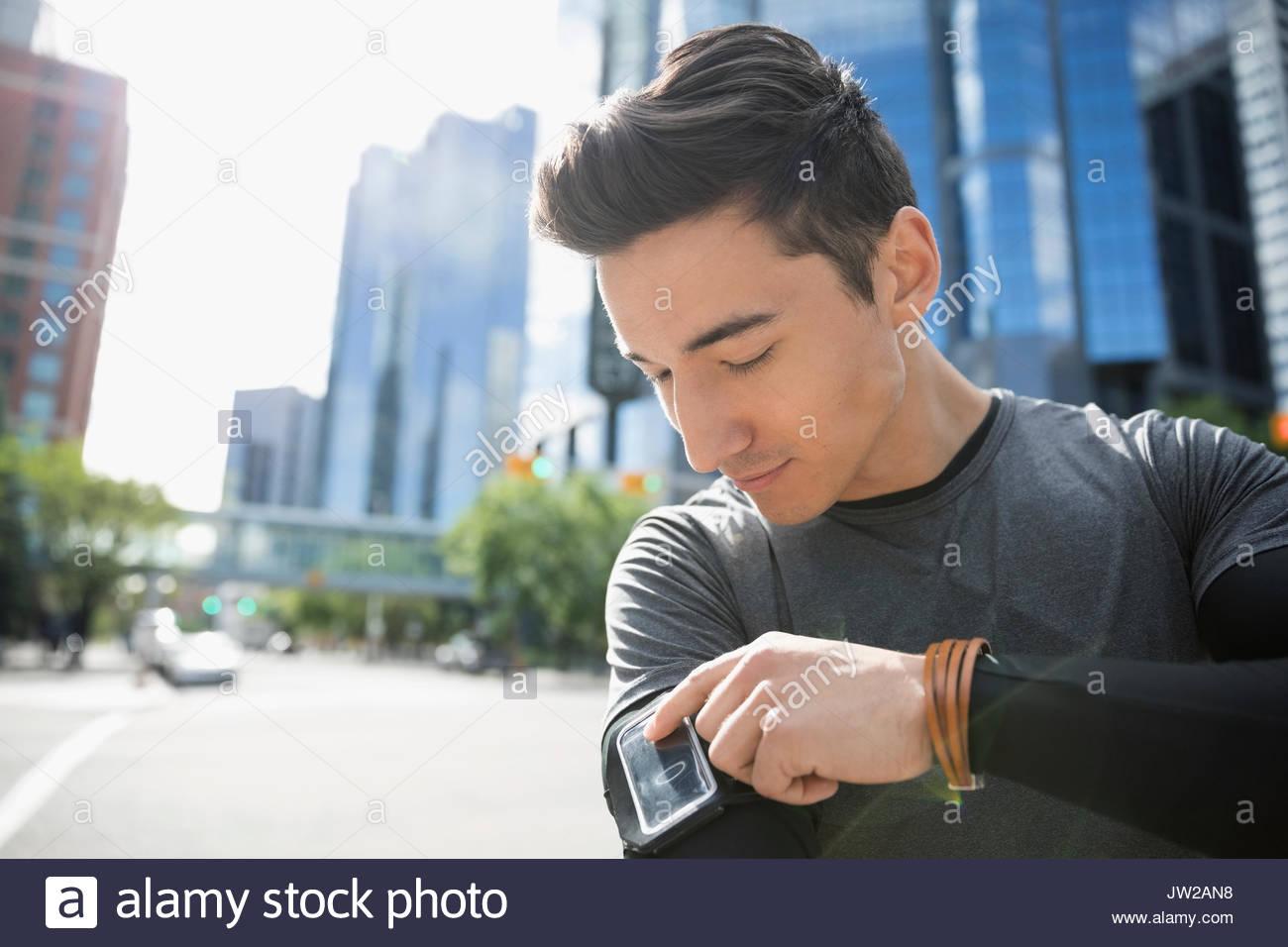 Giovane maschio runner controllo mp3 player fascia braccio sulla soleggiata strada urbana Immagini Stock