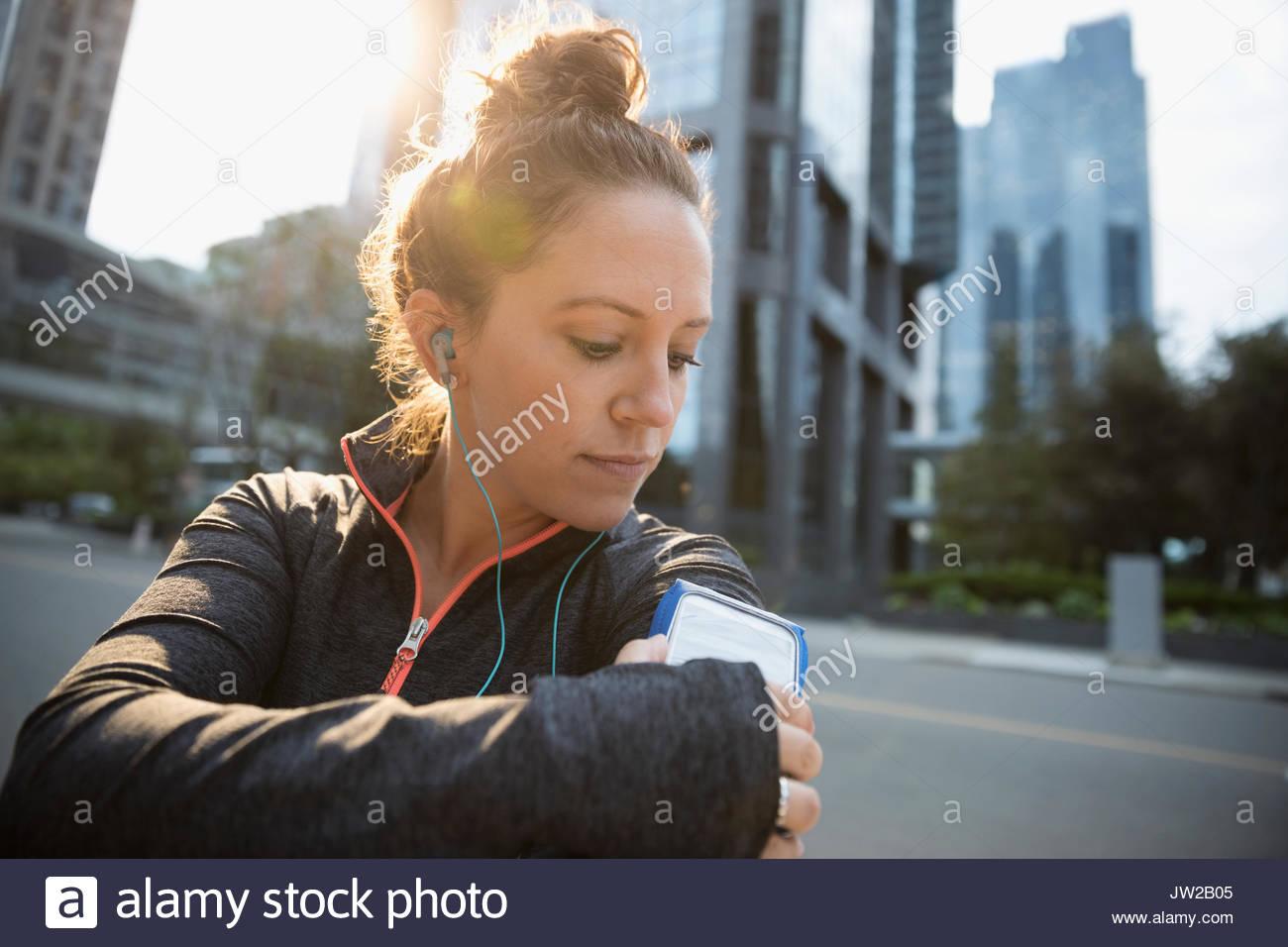 Femmina regolazione runner mp3 player fascia per il braccio, l'ascolto di musica con le cuffie auricolari su strada urbana Immagini Stock