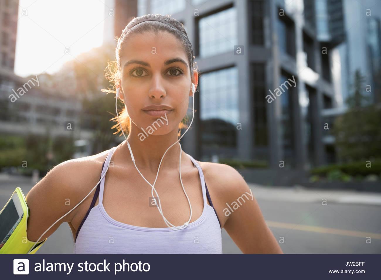 Ritratto di giovane serio femminile l'ascolto di musica con le cuffie auricolari e il lettore mp3 fascia per il braccio Immagini Stock