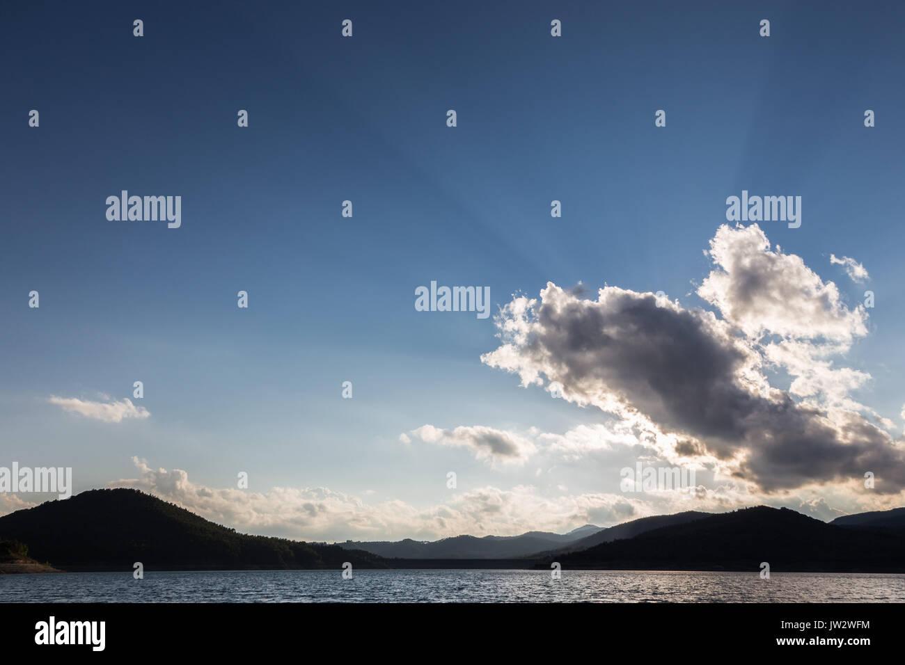 Potenti raggi del sole uscente attraverso alcune nuvole sopra un lago Immagini Stock