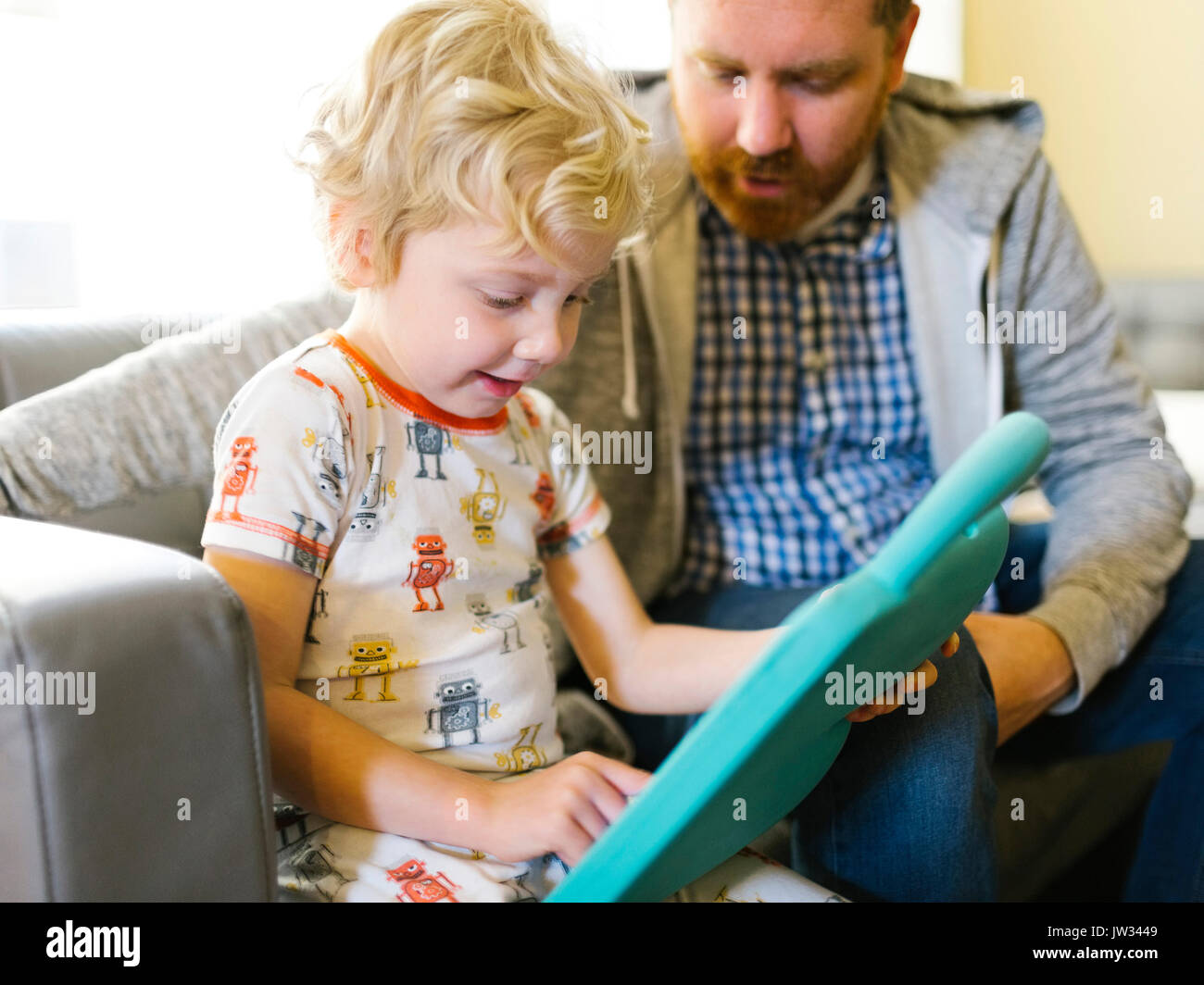Padre e figlio (4-5) giocando con il giocattolo elettronico Immagini Stock