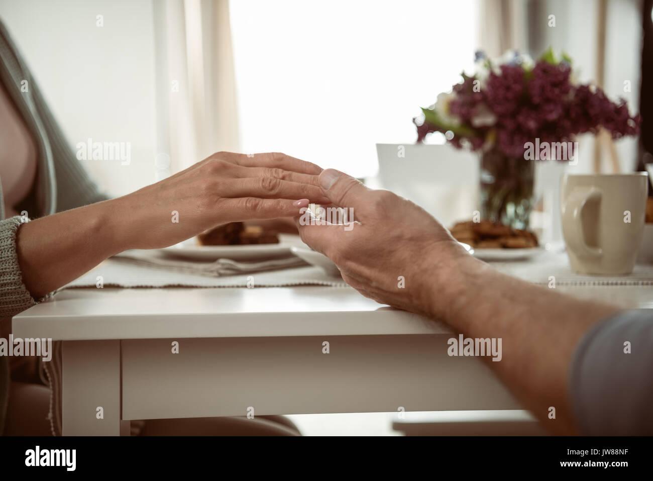 Vista ritagliata della coppia senior tenendo le mani durante la prima colazione Immagini Stock