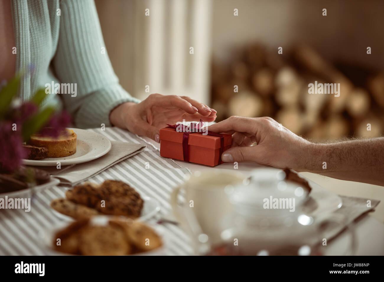 Vista ritagliata della senior marito presentando confezione regalo per sua moglie Immagini Stock
