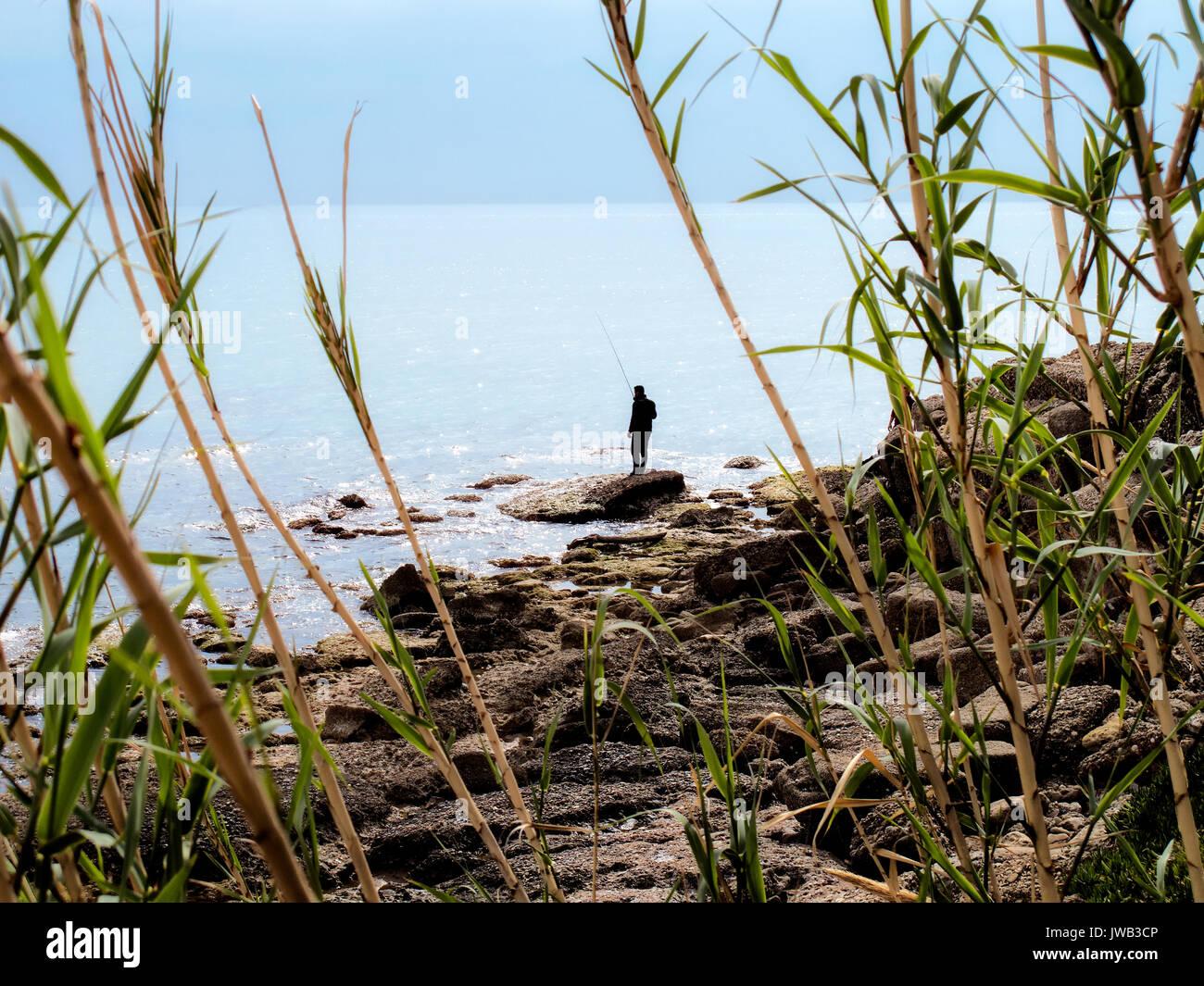 Due pescatori pesca in mare sulla spiaggia rocciosa Immagini Stock